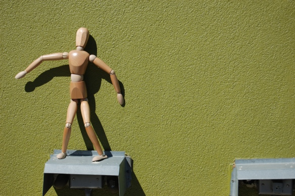 Against a green wall, precariously